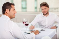 Successful young men has a business lunch in Royalty Free Stock Photos