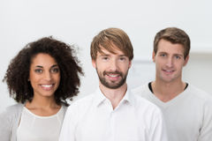 Successful young multiethnic business team. Posing for the camera with their handsome young male leader in the foreground Royalty Free Stock Images