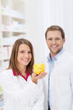 Successful young pharmacist with a piggy bank Royalty Free Stock Image