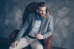 Successful young red bearded elegant businessman in suit with pe. Rfect hairstyle is drinking whiskey indoors, relaxing, sits on leather arm chair, looks harsh stock images