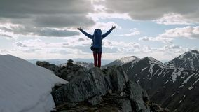 Successful young woman backpacker open arms on mountain peak stock video footage