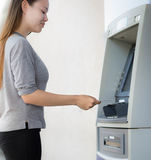 A successful young woman happily withdrawing money from her savings account. Happy to earn money concept. Simple ATM photo Stock Images