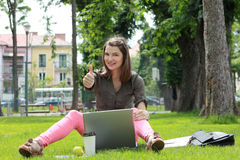 Successful Young Woman. Happy young woman with a laptop rising her right thumb up, outside in an urban park Royalty Free Stock Photo