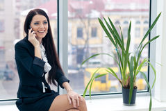 Successful smiling pretty woman at office with mobile cell phone Royalty Free Stock Photography