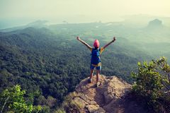 Woman hiker enjoying the view on edge of mountain cliff. Successful young woman hiker enjoying the view on edge of mountain cliff Stock Photos
