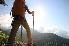 Woman hiker hiking on mountain peak. Successful young woman hiker hiking on mountain peak Stock Photo