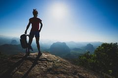 Young woman hiker stand on sunrise mountain peak cliff edge. Successful young woman hiker stand on sunrise mountain peak cliff edge Stock Photography