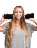 Successful young woman holding two black smartphones isolated on a white background. An attractive girl with phones. stock photo