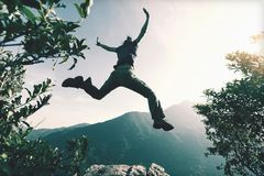 Woman jumping on cliff edge royalty free stock photo