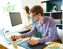 Successful young woman and man working from home Stock Image
