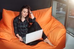 Successful young woman sitting on sofa in office, working on her laptop. Stock Images