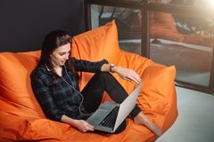 Successful young woman sitting on sofa in office, working on her laptop. Stock Photography