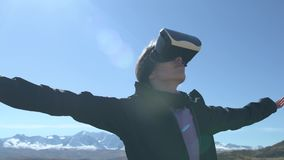 Successful young woman, using virtual reality goggles to tour in mountains, on vacation in summer stock footage