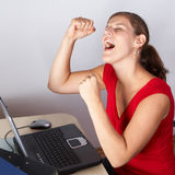 Successfull. Young woman is celebrating with her laptop and a lot of work in front of her Stock Photo