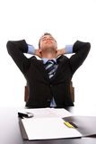 Successfull businessman relaxing over his desk. Isolated in white Royalty Free Stock Photo