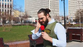 Successfull news reporter with microphone in hand talking live on the street