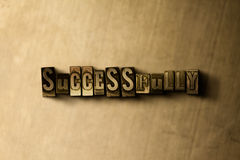 SUCCESSFULLY - close-up of grungy vintage typeset word on metal backdrop. Royalty free stock illustration.  Can be used for online banner ads and direct mail Stock Photos