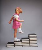 Successfully going up with education. Successfully going from one education level to another - girl going up the stairs of books Royalty Free Stock Photo