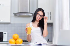 Successfully woman in eyeglasses reading and drinking juice. Royalty Free Stock Photography