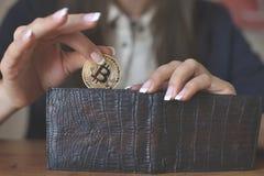 Successfully woman put a Bitcoin into wallet. Crypto coin saving. Savings money. Blockchain technology. Bitcoin cryptocurrency, bitcoin cash, market platform Royalty Free Stock Photos