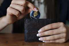 Successfully woman put Ethereum con into wallet. Crypto coin saving. Stock Image