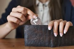Successfully woman put a Litecoin into wallet. Crypto coin saving. Royalty Free Stock Images