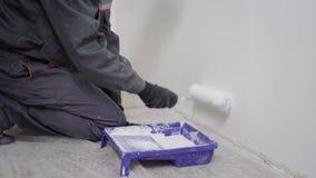 Successi di un costruttore del professionista un rullo in un contenitore con pittura per cambiare il colore delle pareti e fare stock footage
