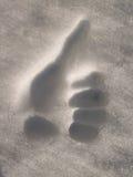 Successo - mano umana che dà i pollici in su nella neve Fotografie Stock Libere da Diritti