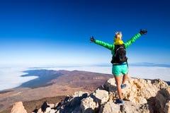 Successo rampicante della donna nella cima della montagna fotografie stock