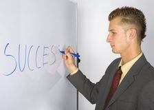 Successs!. Young businessman standing in front of the blackboard and writing word SUCCESS. Side view, gray background Stock Images