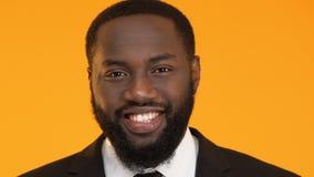 Succesvol Afro-Amerikaans mannetje die die in camera glimlachen op gele achtergrond wordt geïsoleerd stock videobeelden