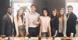 Succesvol commercieel team die camera in bureau bekijken stock fotografie