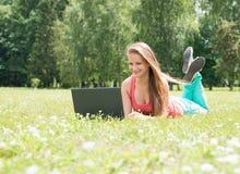 Succesvol meisje online Mooie jonge vrouw met notitieboekje in het park Gelukkige student die op gras met laptop liggen openlucht Royalty-vrije Stock Afbeelding