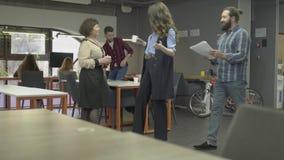 Succesvol team van creatieve jongeren die op gemeenschappelijke taak samenwerken Groep collega's die werkplan bespreken stock video