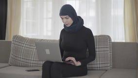 Succesvol zeker meisje in achterkleren en mooi hoofddeksel die met haar laptop zitting aan de bank thuis werken stock videobeelden