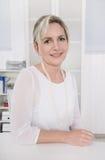 Succesvolle aantrekkelijke blonde oudere onderneemsterzitting bij bureau royalty-vrije stock foto's