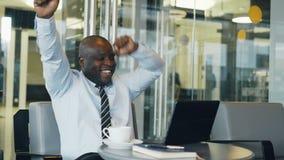 Succesvolle Afrikaanse Amerikaanse zakenman die laptop zeer opgewekt en goed bericht ontvangen en geworden computer met behulp va