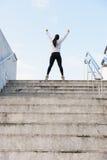 Succesvolle atleet die wapens na het lopen op stedelijke treden opheffen royalty-vrije stock afbeeldingen
