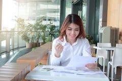 Succesvolle Aziatische bedrijfsvrouw die tegen zijn werk aangaande het bureau in bureau glimlachen Stock Foto
