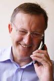 Succesvolle bedrijfsleider die op mobiel glimlacht royalty-vrije stock fotografie