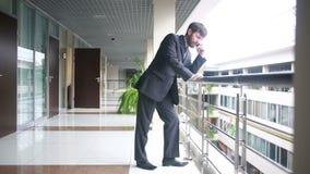 Succesvolle bedrijfsmens die het gesprek hebben van de celtelefoon terwijl status in bureaubinnenland, stock footage