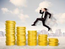 Succesvolle bedrijfsmens die omhoog op gouden muntstukgeld springen Stock Foto's