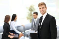 Succesvolle bedrijfsmens die zich met zijn personeel op achtergrond bevinden bij royalty-vrije stock afbeelding