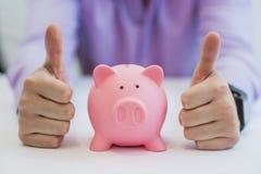 Succesvolle bedrijfsmens met de holdingsduimen van het spaarvarken omhoog in bureau Royalty-vrije Stock Afbeelding