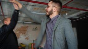 Succesvolle bedrijfsmensen die hoogte vijf in bureau geven Bureau in zolderstijl stock footage