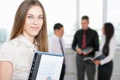 Succesvolle bedrijfsvrouw bij voorgrond en commercieel team bij achtergrond Royalty-vrije Stock Foto's