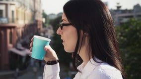 Succesvolle bedrijfsvrouw die afstand, het drinken van koffie en het genieten onderzoeken van stock videobeelden