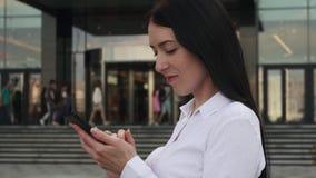 Succesvolle bedrijfsvrouw in wit overhemd gebruikend smartphone en glimlachend in stad stock videobeelden