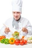Succesvolle chef-koksalade met een kom en een houten lepel Stock Foto