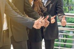 Succesvolle commerciële groep met duimen omhoog bij de stad royalty-vrije stock afbeeldingen